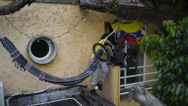 Venezuelan Olympic medalist Stefany Hernandez, a BMX racing cyclist, returns her bike to her home after training on her roof, where she enjoys the view and perform certain moves that she cannot do on the uneven pavement, in Caracas, Venezuela, Saturday, April 25, 2020. Despite a quarantine to curb the spread of COVID-19, Hernandez trains three times a week in hopes of qualifying for the 2021 Tokyo Summer Olympics. (AP Photo/Matias Delacroix)