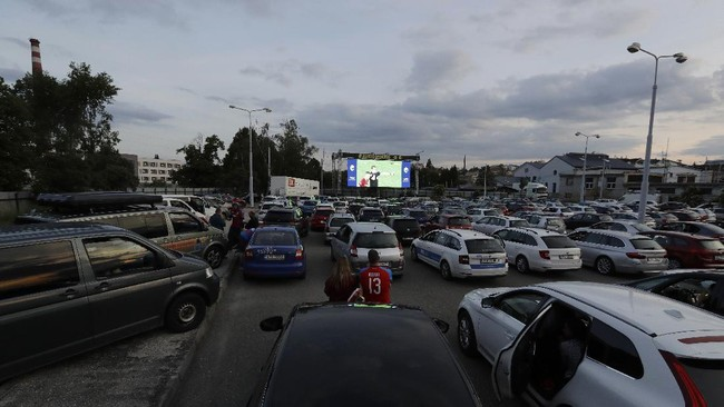 Fans watch the Czech first division soccer match between Viktoria Plzen and Sparta Praha at a drive-in movie theater in Pilsen, Czech Republic, Wednesday, May 27, 2020. The match is being played live where fans can watch it on the screen at the drive in theater due to the highly contagious coronavirus. (AP Photo/Petr David Josek)