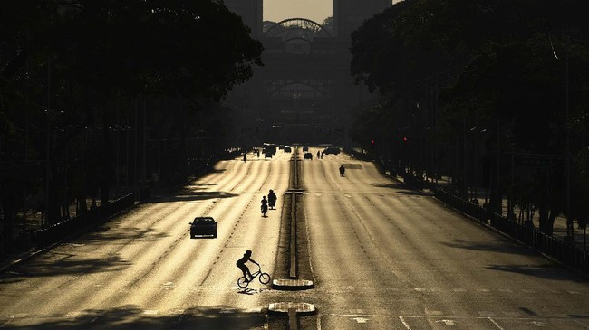 Venezuelan Olympic medalist Stefany Hernandez, a BMX racing cyclist, rides across an empty Bolivar Avenue amid the new coronavirus pandemic in Caracas, Venezuela, Saturday, April 25, 2020. Despite a quarantine to curb the spread of COVID-19, Hernandez trains three times a week in hopes of qualifying for the 2021 Tokyo Summer Olympics. (AP Photo/Matias Delacroix)