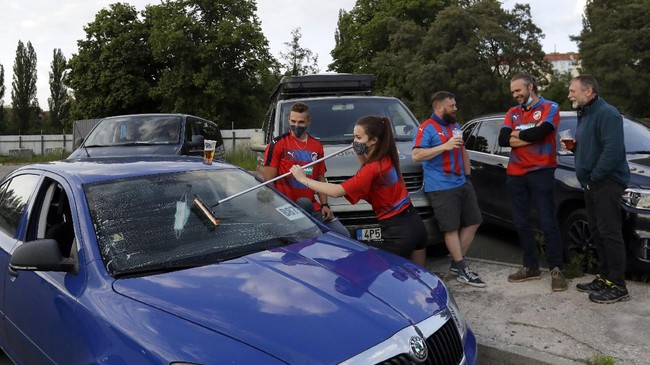 A girl washes a car windshield before the Czech first division soccer match between Viktoria Plzen and Sparta Praha at a drive-in movie theater in Pilsen, Czech Republic, Wednesday, May 27, 2020. The match is being played live where fans can watch it on the screen at the drive in theater due to the highly contagious coronavirus. (AP Photo/Petr David Josek)