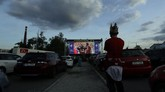 A fan watches the Czech first division soccer match between Viktoria Plzen and Sparta Praha at a drive-in movie theater in Pilsen, Czech Republic, Wednesday, May 27, 2020. The match is being played live where fans can watch it on the screen at the drive in theater due to the highly contagious coronavirus. (AP Photo/Petr David Josek)