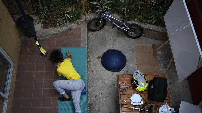 Venezuelan Olympic medalist Stefany Hernandez, a BMX racing cyclist, stretches at home in Caracas, Venezuela, Saturday, April 25, 2020. Despite a quarantine to curb the spread of COVID-19, Hernandez trains three times a week in hopes of qualifying for the 2021 Tokyo Summer Olympics. (AP Photo/Matias Delacroix)