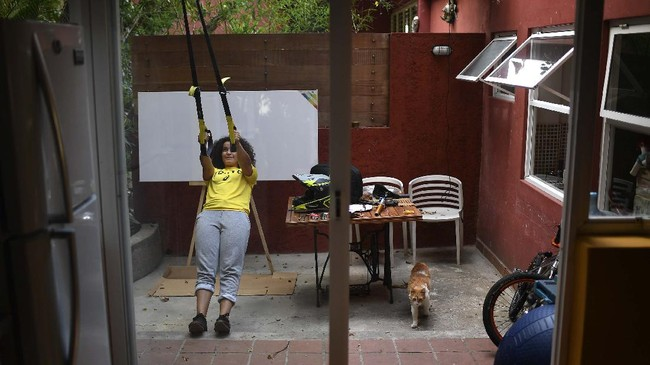 Venezuelan Olympic medalist Stefany Hernandez, a BMX racing cyclist, stretches at her home in Caracas, Venezuela, Saturday, April 25, 2020. Despite a quarantine to curb the spread of COVID-19, Hernandez trains three times a week in hopes of qualifying for the 2021 Tokyo Summer Olympics. (AP Photo/Matias Delacroix)
