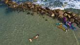 Members of the Israeli Mermaids Community swim with mermaid tails at the beachfront in Bat Yam, near Tel Aviv, Israel, Saturday, May 23, 2020. Members of the Israeli mermaid community gathered at the beachfront to mark the beginning of the bathing season. (AP Photo/Oded Balilty)