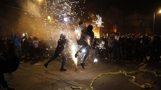 Protesters set off fireworks as a fire burns at the Minneapolis police 3rd Precinct building Thursday, May 28, 2020, in Minneapolis. Violent protests over the death of George Floyd, a black man who died in police custody Monday, broke out in Minneapolis for a third straight night. (AP Photo/Julio Cortez)