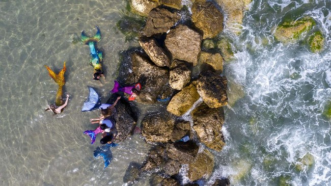 Members of the Israeli Mermaids Community wear mermaid tails at the beachfront in Bat Yam, near Tel Aviv, Israel, Saturday, May 23, 2020. Members of the Israeli mermaid community gathered at the beachfront to mark the beginning of the bathing season. (AP Photo/Oded Balilty)