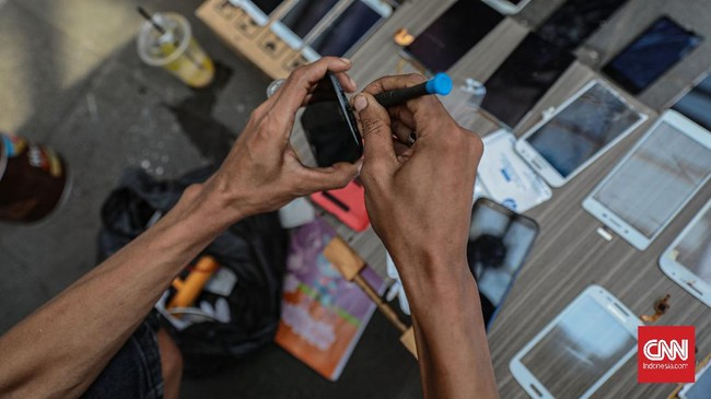 Sejumlah penjual jasa servis handphone Pusat Grosir Cililitan mempromosikan jasa servis handphone di pinggir jalan raya Cililitan, Jakarta, Jumat, 29 Mei 2020. Selama PSBB berlangsung, para para penjual jasa servis tersebut menawarkan jasanya hingga ke tepi jalan karena larangan membuka gerai  di pusat perbelanjaan tersebut. CNN Indonesia/Bisma Septalisma