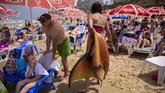 A member of the Israeli Mermaids Community carries her mermaid tail after a swim at the beachfront in Bat Yam, near Tel Aviv, Israel, Saturday, May 23, 2020. Members of the Israeli mermaid community gathered at the beachfront to mark the beginning of the bathing season. (AP Photo/Oded Balilty)
