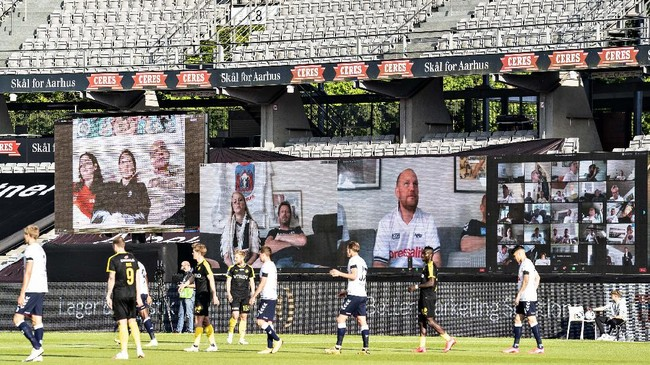 People watch the Danish Super League soccer match between AGF and Randers FC via videolink, at Ceres Park in Aarhus, Denmark, Thursday, May 28, 2020. The match is the first to be played after the shutdown due to the outbreak of the coronavirus and is being played without spectators and with restrictions. (Henning Bagger/Ritzau Scanpix via AP)