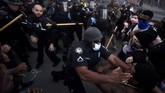 Police officers and protesters clash near CNN Center, Friday, May 29, 2020, in Atlanta, in response to George Floyd's death in police custody in Minneapolis on Memorial Day. The protest started peacefully earlier in the day before demonstrators clashed with police. (AP Photo/Mike Stewart)