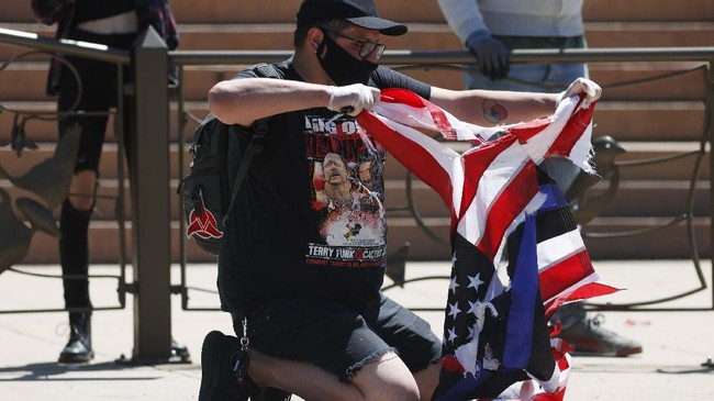 A participant destroys a thin blue line American flag used to honor police officers during a protest outside the State Capitol over the death of George Floyd, a handcuffed black man in police custody in Minneapolis, Friday, May 29, 2020, in Denver. More than 1,000 protesters walked from the Capitol down the 16th Street pedestrian mall during the protest. (AP Photo/David Zalubowski)
