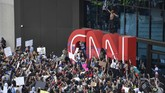 EDS NOTE: OBSCENITY - Demonstrators paint on the CNN logo during a protest march, Friday, May 29, 2020, in Atlanta, in response to the Memorial Day death of George Floyd in police custody in Minneapolis. The protest started peacefully earlier in the day before demonstrators clashed with police. (AP Photo/Mike Stewart)