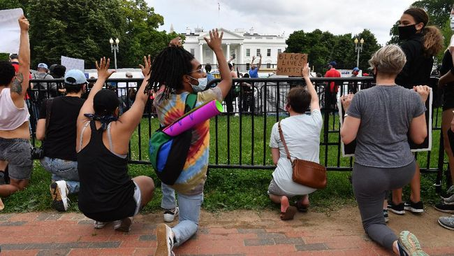 Protesters kneel as they gather outside the White House in Washington, DC, on May 29, 2020 in a demonstration over the death of George Floyd, a black man who died after a white policeman kneeled on his neck for several minutes. - Demonstrations are being held across the US after George Floyd died in police custody on May 25. (Photo by Nicholas Kamm / AFP)
