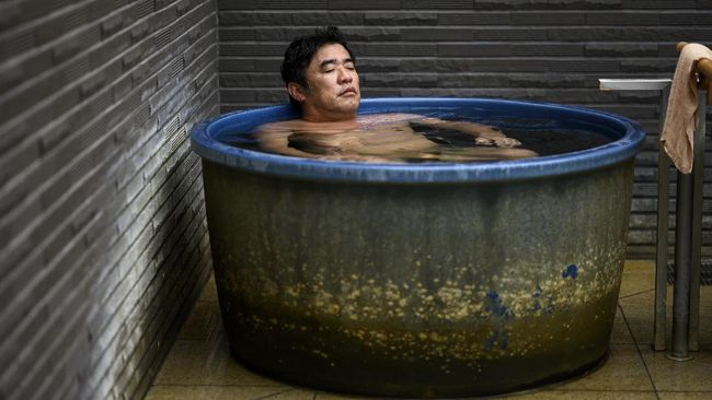 In this picture taken on May 29, 2020, Masazumi Kato relaxes in a tub at a Japanese hot spring or onsen in Yokohama, Kanagawa prefecture. - With the lifting of a nationwide state of emergency over the virus, Japan's onsen -- large bathhouses where patrons bathe naked in a series of warm pools and tubs -- are gradually reopening. (Photo by Behrouz MEHRI / AFP) / TO GO WITH AFP STORY 'JAPAN-VIRUS-HEALTH-LIFESTYLE-BATH' FOCUS BY HIROSHI HIYAMA