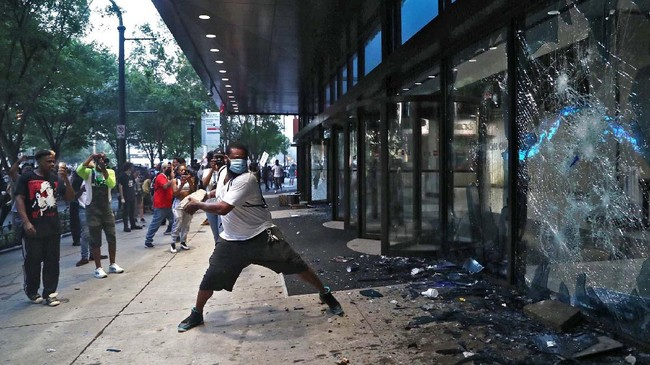 A protester smashes a window at the CNN center Friday May 29, 2020 in Atlanta. They carried signs and chanted their messages of outrage over the death of George Floyd in Minneapolis. (Alyssa Pointer/Atlanta Journal-Constitution via AP)