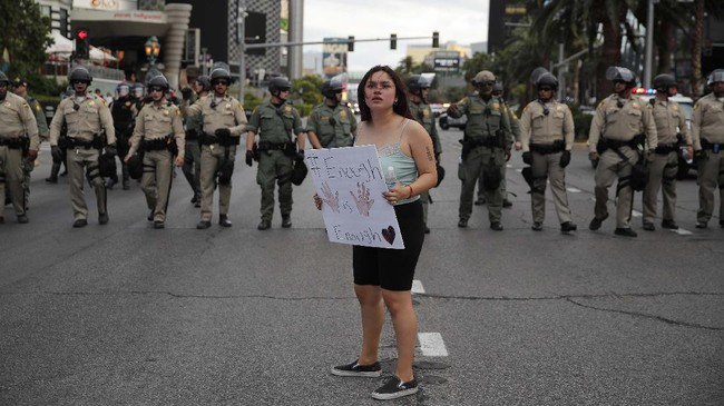 A woman protesting the death of George Floyd stands in front of a line of police along Las Vegas Boulevard, Friday, May 29, 2020, in Las Vegas. Floyd died on Memorial Day while in the custody of the Minneapolis police. (AP Photo/John Locher)