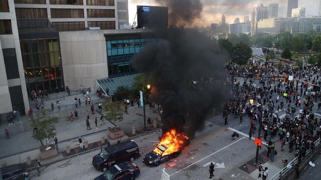 A police car burns after protesters marched to the Georgia State Capitol and returned to the area around the Centennial Olympic Park and CNN center where some confronted police Friday, May 29, 2020, in Atlanta. The protesters carried signs and chanted  messages of outrage over the death of George Floyd, a handcuffed back man who died Memorial Day in the custody of the Minneapolis police. (Alyssa Pointer/Atlanta Journal-Constitution via AP)
