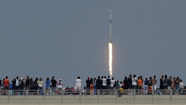 Spectators watch from a bridge in Titusville, Fla. as SpaceX Falcon 9 lifts off with NASA astronauts Doug Hurley and Bob Behnken in the Dragon crew capsule, Saturday, May 30, 2020 from the Kennedy Space Center at Cape Canaveral, Fla. The two astronauts are on the SpaceX test flight to the International Space Station. For the first time in nearly a decade, astronauts blasted towards orbit aboard an American rocket from American soil, a first for a private company. (AP Photo/Charlie Riedel)