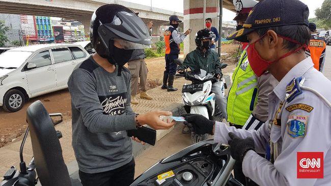 Petugas gabungan dari Dinas Perhubungan, Satpol PP, hingga kepolisian memeriksa kelengkapan administrasi bagi warga yang hendak melintas ke wilayah DKI Jakarta, Minggu (31/5). Bagi warga yang tidak ber-KTP Jabodetabek dan tidak membawa surat izin keluar masuk (SIKM) Jakarta akan diputar balik.