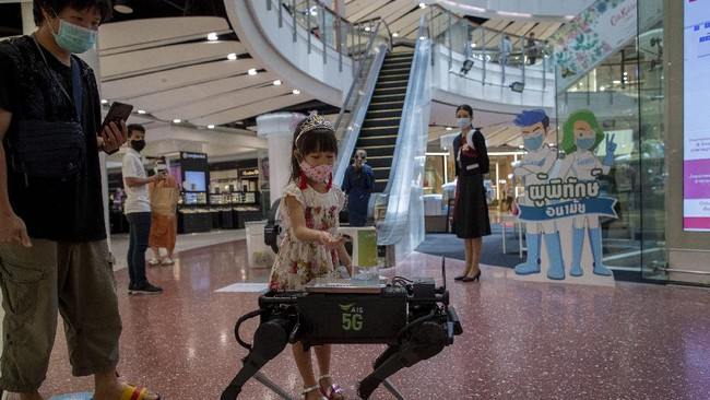 A child disinfects her hands from a mobile robot that carries a container of sanitization liquid at Central World, an upmarket shopping mall in Bangkok, Thailand, Wednesday, May 27, 2020. Thai government continues to ease restrictions related to running business in capital Bangkok that were imposed weeks ago to combat the spread of COVID-19. (AP Photo/Gemunu Amarasinghe)