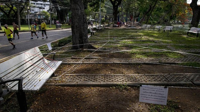 People jog past park seats cordoned off to prevent people gathering in groups at Lumpini Park Bangkok, Thailand, Monday, May 18, 2020. Thai parks have reopened with strict implementation of physical distancing and compulsory use of masks. Group exercising remain banned. (AP Photo/ Gemunu Amarasinghe)