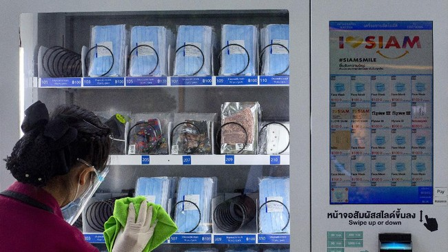 Wearing face shield, mask and gloves, an employee cleans a face mask vending machine at the Siam Paragon shopping mall in Bangkok, Thailand, Tuesday, May 19, 2020. As part of the country's COVID-19 response, the Thai government requires use of face masks in public. Patrons without face masks are denied entry to shops, restaurants and other venues. (AP Photo/Gemunu Amarasinghe)