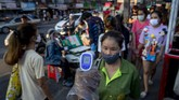 A police officer measures body temperatures of visitors entering a market area in Bangkok, Thailand, Tuesday, May 12, 2020. People with body temperature exceeding 37.5 degree Celsius, (99.5 Fahrenheit) or potential symptoms of COVID-19 are typically barred from entering communal areas. (AP Photo/Gemunu Amarasinghe)
