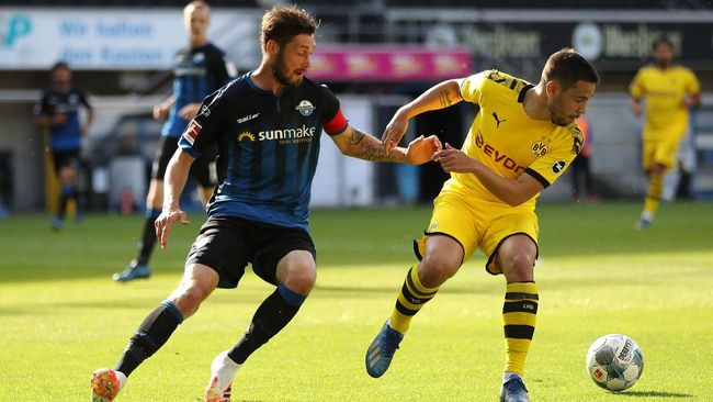 Christian Paderborn's German defender Christian Strohdiek vies with Dortmund's Portuguese defender Raphael Guerreiro during the German first division Bundesliga football match SC Paderborn 07 and Borussia Dortmund at Benteler Arena in Paderborn on May 31, 2020. (Photo by Lars Baron / POOL / AFP) / DFL REGULATIONS PROHIBIT ANY USE OF PHOTOGRAPHS AS IMAGE SEQUENCES AND/OR QUASI-VIDEO