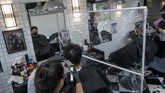 Barbers divided by a plastic partitions cut hair in a small shop in Bangkok, Thailand, Saturday, May 23, 2020. The Thai government continues to ease restrictions on businesses and services in Bangkok that were imposed weeks ago to combat the spread of the coronavirus. (AP Photo/Gemunu Amarasinghe)