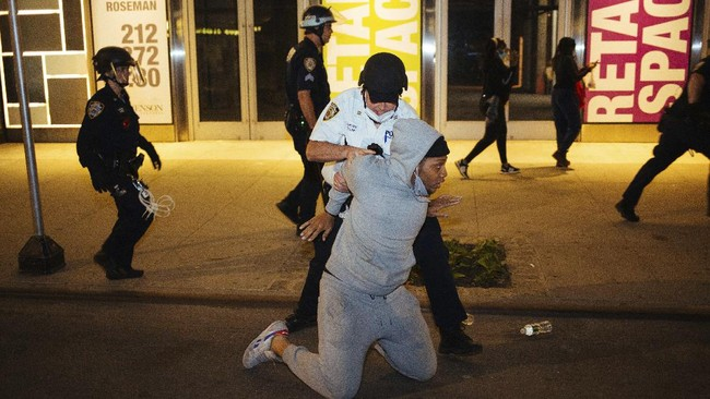 Police take a man into custody Sunday, May 31, 2020, in New York. Demonstrators took to the streets of New York City to protest the death of George Floyd, who died May 25 after he was pinned at the neck by a Minneapolis police officer. (AP Photo/Kevin Hagen).