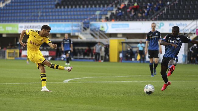 Achraf Hakimi Mouh of Borussia Dortmund scores his teams fourth goal during the German Bundesliga soccer match between SC Paderborn 07 and Borussia Dortmund at Benteler Arena in Paderborn, Germany, Sunday, May 31, 2020. Because of the coronavirus outbreak all soccer matches of the German Bundesliga take place without spectators. (Lars Baron/Pool via AP)