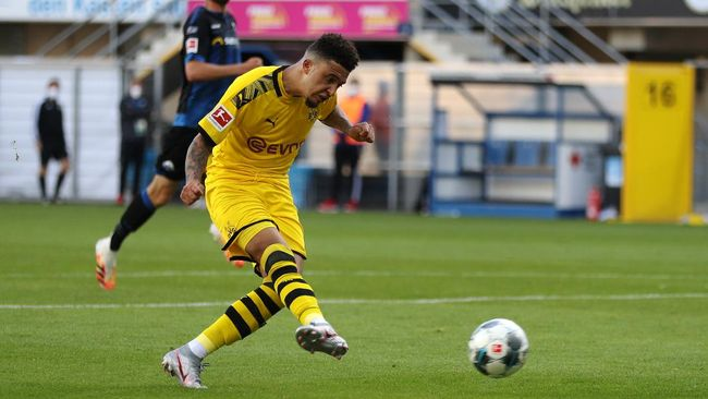 Dortmund's English midfielder Jadon Sancho scores his teams sixth goal past Paderborn's German goalkeeper Leopold Zingerle during the German first division Bundesliga football match SC Paderborn 07 and Borussia Dortmund at Benteler Arena in Paderborn on May 31, 2020. - Dortmund's English midfielder Jadon Sancho scores his teams sixth goal past Paderborn's German goalkeeper Leopold Zingerle (Photo by Lars Baron / POOL / AFP) / DFL REGULATIONS PROHIBIT ANY USE OF PHOTOGRAPHS AS IMAGE SEQUENCES AND/OR QUASI-VIDEO