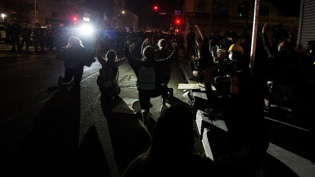 Protesters wait to be arrested Sunday, May 31, 2020, in Los Angeles, during a demonstration over the death of George Floyd, who died May 25 after he was pinned at the neck by a Minneapolis police officer. (AP Photo/Ringo H.W. Chiu)
