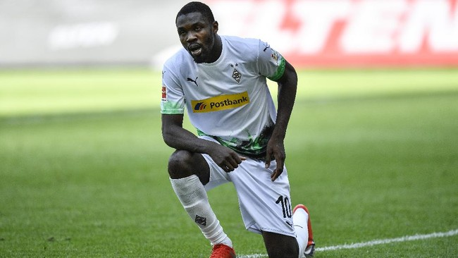 Moenchengladbach's Marcus Thuram gets up after taking the knee after scoring his side's second goal during the German Bundesliga soccer match between Borussia Moenchengladbach and Union Berlin in Moenchengladbach, Germany, Sunday, May 31, 2020. The German Bundesliga becomes the world's first major soccer league to resume after a two-month suspension because of the coronavirus pandemic. (AP Photo/Martin Meissner, Pool)