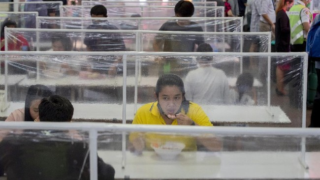 Customers eat in a food court at communal tables divided by plastic partitions in Bangkok, Thailand, Tuesday, May 19, 2020. Bangkok's beloved food hubs come alive as restrictions ease on food vendors. (AP Photo/ Gemunu Amarasinghe)