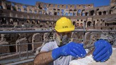 A restorer works inside the Colosseum in Rome, Monday, June 1, 2020, during a press conference announcing the reopening to the public of one of Italy's most visited monument, after more of two months of lockdown for the coronavirus pandemics. The Colosseum, Palatine, Roman Forum and Domus Aurea reopens to the public on 1 June with some access restrictions for visitors. (AP Photo/Domenico Stinellis)