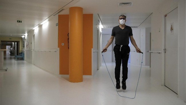 In this Wednesday, May 27, 2020 photo, a medical worker Mohamed jumps rope as he attend a training session with French boxer Hassan N'Dam at the Villeneuve-Saint-Georges hospital, outside Paris. A world champion French boxer is taking his skills to hospitals, coaching staff to thank the medical profession for saving his father-in-law from the virus, and giving them new confidence and relief from their stressful jobs. (AP Photo/Christophe Ena)