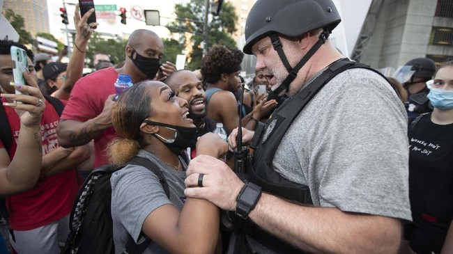 An Atlanta police officer speaks to a protester during a demonstration Monday, June 1, 2020, in Atlanta over the death of George Floyd, who died after being restrained by Minneapolis police officers on May 25. (AP Photo/John Bazemore)