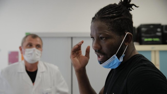 In this Wednesday, May 27, 2020 photo, Five-time World Middle Weight boxing Champion France's Hassan N'Dam speaks with medical staff during a training session, at the Villeneuve-Saint-Georges hospital, outside Paris. A world champion French boxer is taking his skills to hospitals, coaching staff to thank the medical profession for saving his father-in-law from the virus, and giving them new confidence and relief from their stressful jobs. (AP Photo/Christophe Ena)