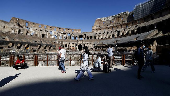 Members of the media walk inside the ancient Colosseum during a press preview for the reopening of the museum, in Rome, Monday, June 1, 2020. The Colosseum, one of Italy's most popular tourist attractions, reopens on Monday to visitors after three months of shutdown following COVID-19 containment measures. (Cecilia Fabiano/LaPresse via AP)