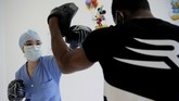 In this Wednesday, May 27, 2020 photo, medical worker Kenza, left, boxes during a training session with French boxer Hassan N'Dam at the Villeneuve-Saint-Georges hospital, outside Paris. A world champion French boxer is taking his skills to hospitals, coaching staff to thank the medical profession for saving his father-in-law from the virus, and giving them new confidence and relief from their stressful jobs. (AP Photo/Christophe Ena)