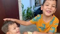 <p>Kata Mama Titi, Kakak Juna dan Kai lagi minta difoto di depan pintu nih, Bunda. Kakak Juna elus-elus kepala adiknya ya? <em>He-he-he</em> (Foto: Instagram @titikamall)</p>