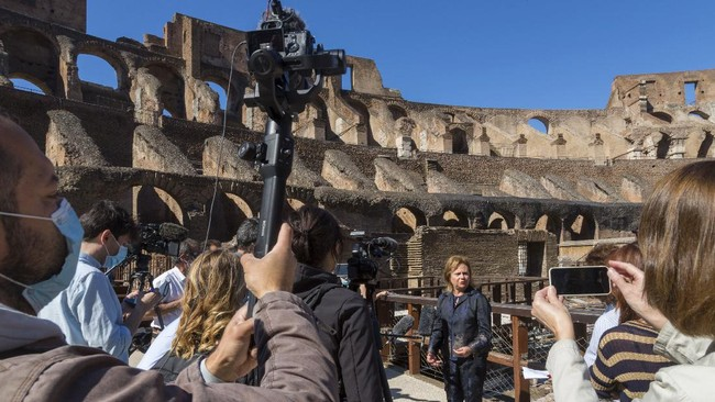 Alfonsina Russo, center, director of the Colosseum Archaeological Park, speaks to media inside the Colosseum in Rome, Monday, June 1, 2020, to announce the reopening to the public of one of Italy's most visited monument, after more of two months of lockdown for the coronavirus pandemics. The Colosseum, Palatine, Roman Forum and Domus Aurea reopens to the public on 1 June with some access restrictions for visitors. (AP Photo/Domenico Stinellis)