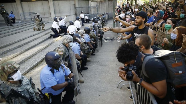 Philadelphia police and National Guard take a knee at the suggestion of Philadelphia Police Deputy Commissioner Melvin Singleton, unseen, outside Philadelphia Police headquarters in Philadelphia, Monday, June 1, 2020 during a march calling for justice over the death of George Floyd, Floyd died after being restrained by Minneapolis police officers on May 25. (AP Photo/Matt Rourke)