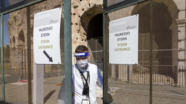 A member of the staff closes one of the gates of the Colosseum in Rome, Monday, June 1, 2020, during a press conference announcing the reopening to the public of one of Italy's most visited monument, after more of two months of lockdown for the coronavirus pandemics. The Colosseum, Palatine, Roman Forum and Domus Aurea reopens to the public on 1 June with some access restrictions for visitors. (AP Photo/Domenico Stinellis)