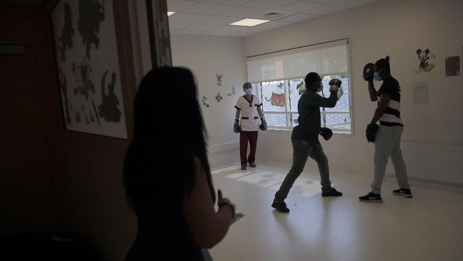 In this Wednesday, May 27, 2020 photo, Temy, a medical worker, center, boxes during a training session with French boxer Hassan N'Dam, right, at the Villeneuve-Saint-Georges hospital, outside Paris. A world champion French boxer is taking his skills to hospitals, coaching staff to thank the medical profession for saving his father-in-law from the virus, and giving them new confidence and relief from their stressful jobs. (AP Photo/Christophe Ena)