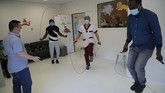 In this Wednesday, May 27, 2020 photo, medical staff jump rope as they attend a training with French boxer Hassan N'Dam, centre left, at the Villeneuve-Saint-Georges hospital, outside Paris. A world champion French boxer is taking his skills to hospitals, coaching staff to thank the medical profession for saving his father-in-law from the virus, and giving them new confidence and relief from their stressful jobs. (AP Photo/Christophe Ena)