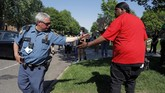 Gemini Stone Pollard, right shakes hands with a police officer Monday, June 1, 2020, in St. Paul, Minn. Protests continued following the death of George Floyd, who died after being restrained by Minneapolis police officers on Memorial Day. (AP Photo/Julio Cortez)