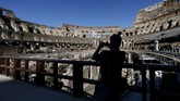 A journalist uses a smartphone inside the ancient Colosseum during a press preview for the reopening of the archeological museum, in Rome, Monday, June 1, 2020. The Colosseum, one of Italy's most popular tourist attractions, reopens on Monday to visitors after three months of shutdown following COVID-19 containment measures. (Cecilia Fabiano/LaPresse via AP)