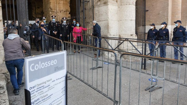 Alfonsina Russo, left wearing black face mask, director of the Colosseum Archaeological Park, opens the main entrance gate of Colosseum in Rome, Monday, June 1, 2020, reopening to the public one of Italy's most visited monument, after more of two months of lockdown for the coronavirus pandemics. The Colosseum, Palatine, Roman Forum and Domus Aurea reopens to the public on 1 June with some access restrictions for visitors. (AP Photo/Domenico Stinellis)